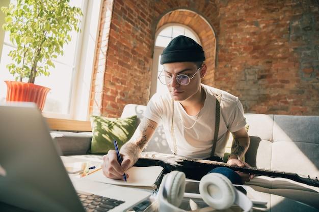 Mężczyzna uczący się w domu podczas kursów muzycznych online.