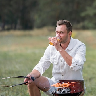 Mężczyzna uczestniczy w grillu na świeżym powietrzu i pije piwo