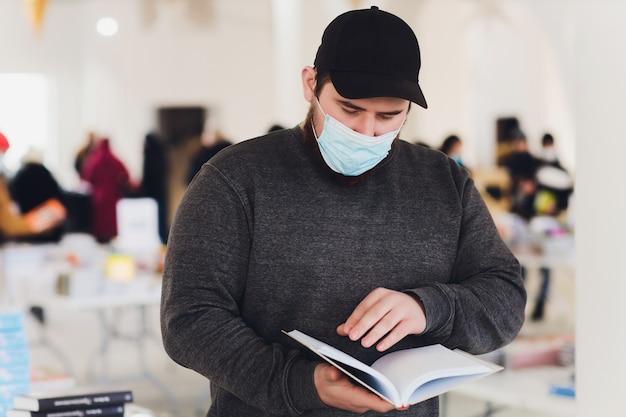 Mężczyzna uczy się czytania książki w bibliotece podczas pandemii koronawirusa covid19, nosi ochronną medyczną maskę na twarz. nowa norma dla bibliotekarza.