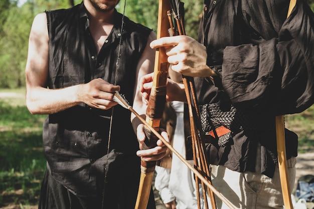 Mężczyzna uczy strzelać z łuku chłopiec trzyma łuk w dłoniach
