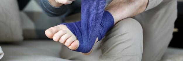 Mężczyzna udzielił pierwszej pomocy, przewracając niebieską taśmę bandażową na zbliżenie stopy