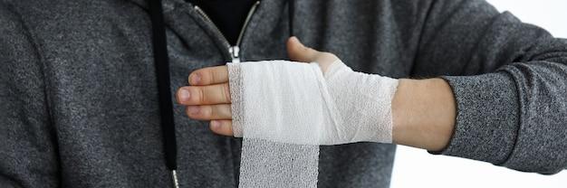 Mężczyzna udzielił sobie pierwszej pomocy zwijania taśmy bandażowej na zbliżenie nadgarstka