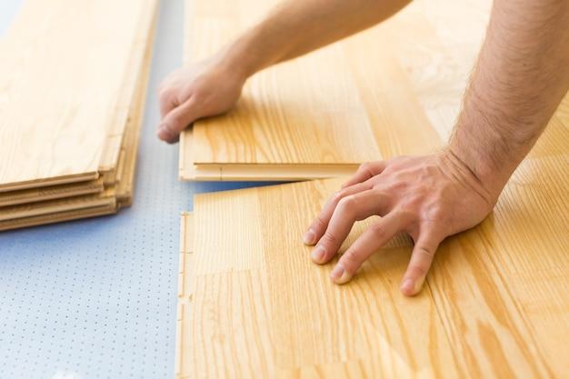 Mężczyzna układa nowe deski podłogowe, z bliska