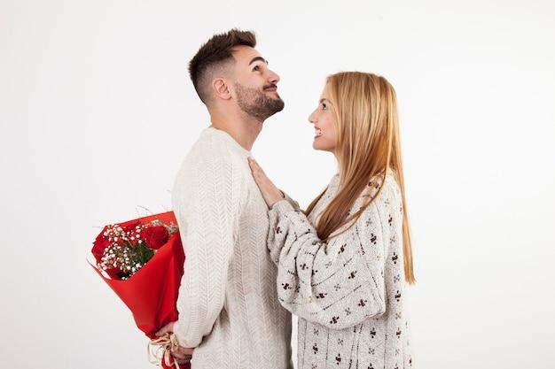 Mężczyzna ukrywa bukiet od kobiety