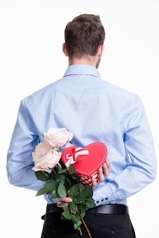 Mężczyzna ukrywa kwiat za plecami na białym tle.