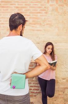 Mężczyzna ukrywa niespodzianka prezent od jej dziewczyny czytelniczej książki
