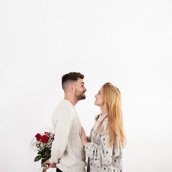 Mężczyzna ukrywa róże od kobiety