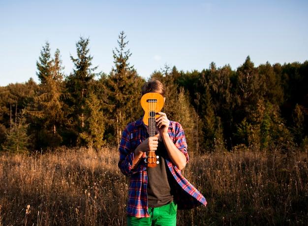 Mężczyzna ukrywszy twarz gitarą ukulele