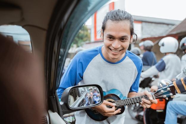 Mężczyzna uliczny muzyk żebrzący o pieniądze z sygnalizacji świetlnej