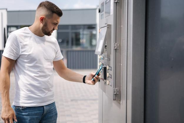 Mężczyzna umieścił kartę platic do płacenia na zewnątrz w samoobsługowej myjni samochodowej