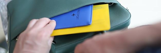 Mężczyzna umieszcza bilety lotnicze i paszport w torbie zbliżenie