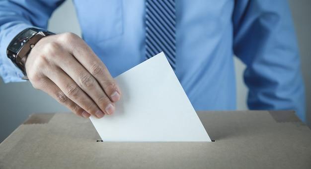 Mężczyzna umieszcza kartę do głosowania w urnie wyborczej. demokracja. wolność