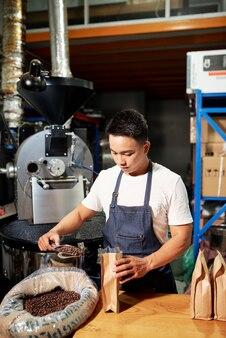 Mężczyzna umieszcza paloną kawę w opakowaniach