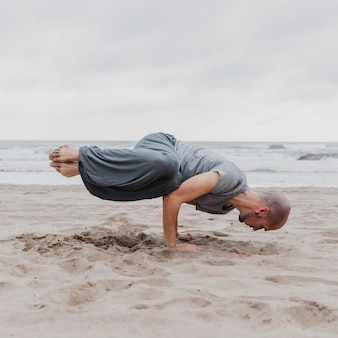 Mężczyzna uprawiający jogę na plaży