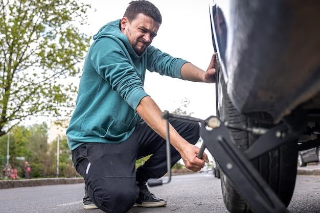 Mężczyzna usiłujący zmienić oponę w samochodzie, walcząc z kluczem do kół, aby poluzować nakrętki.