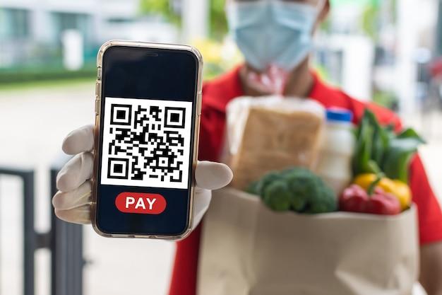 Mężczyzna usługi dostarczania żywności trzymający torbę zestawu świeżej żywności czeka na klienta zeskanować kod qr na telefonie komórkowym do płatności online w drzwiach do domu, usługa szybkiej dostawy, ekspresowa dostawa, koncepcja zakupów online