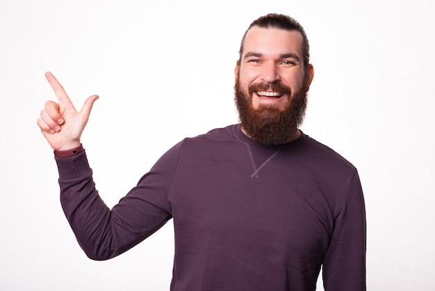 Mężczyzna uśmiecha się do kamery i wskazuje na wolne miejsce