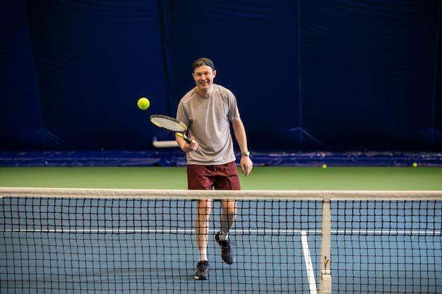 Mężczyzna uśmiecha się i odbija piłkę tenisową na swojej rakiecie podczas przerwy w grze
