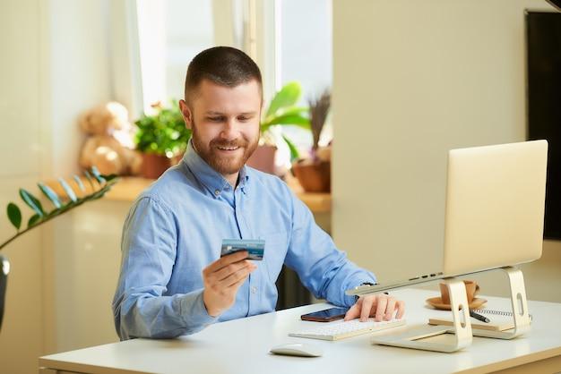 Mężczyzna uśmiecha się i patrząc na swoją kartę kredytową przed laptopem w domu.