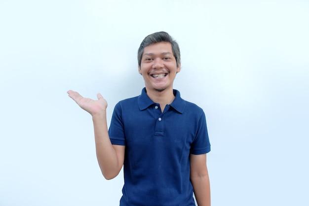 Mężczyzna uśmiecha się i podnosi rękę, patrząc na kamerę