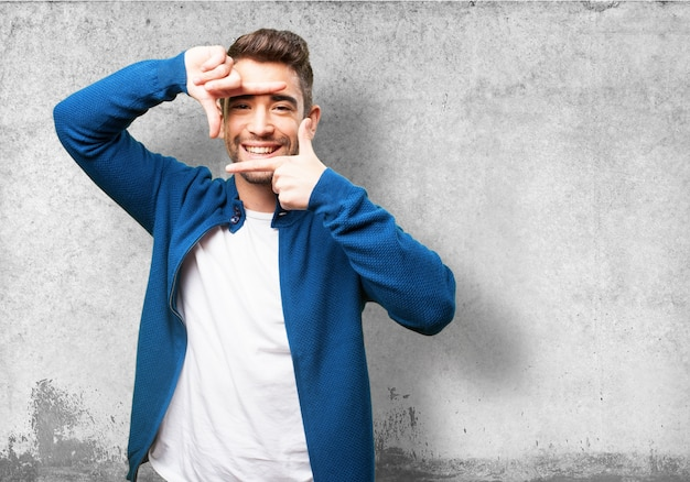 Mężczyzna uśmiecha się podczas dokonywania ramkę palcami