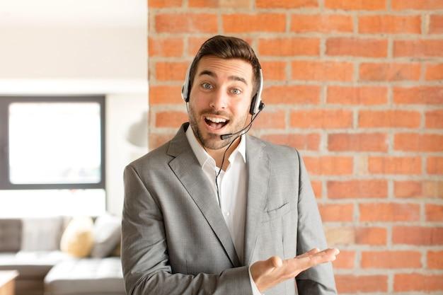 Mężczyzna uśmiecha się radośnie, czuje się szczęśliwy i pokazuje koncepcję w przestrzeni kopii z dłoni