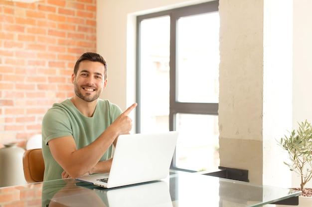 Mężczyzna uśmiecha się radośnie, czuje się szczęśliwy i wskazuje na bok i do góry, pokazując obiekt w przestrzeni kopii