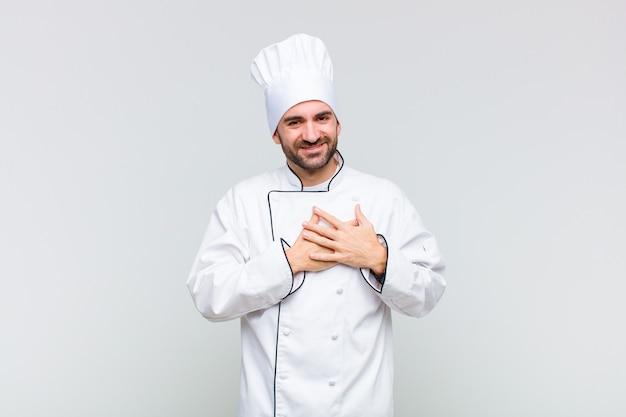 Mężczyzna uśmiecha się radośnie i trzymając się za ręce blisko serca