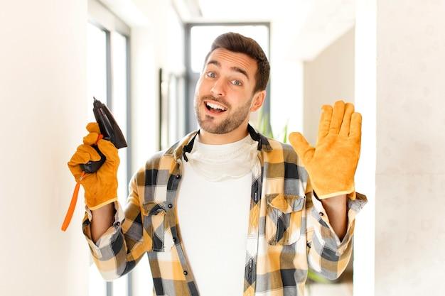 Mężczyzna uśmiecha się radośnie i wesoło, macha ręką i wita się lub żegna
