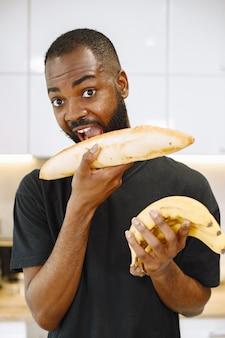 Mężczyzna uśmiecha się trzymając chleb, jakby go gryzł