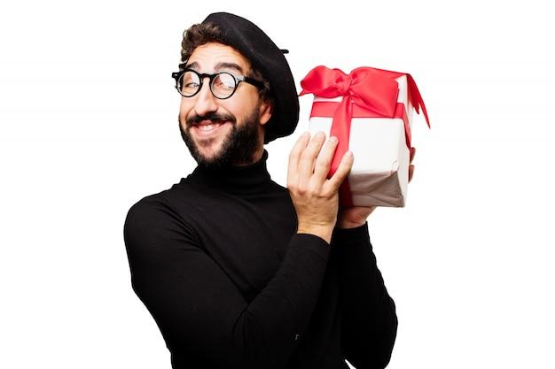 Mężczyzna uśmiecha się z białym prezent z czerwoną kokardką