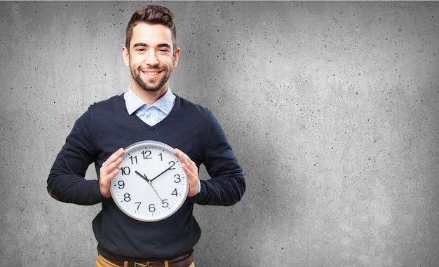 Mężczyzna uśmiecha się z dużym zegarem