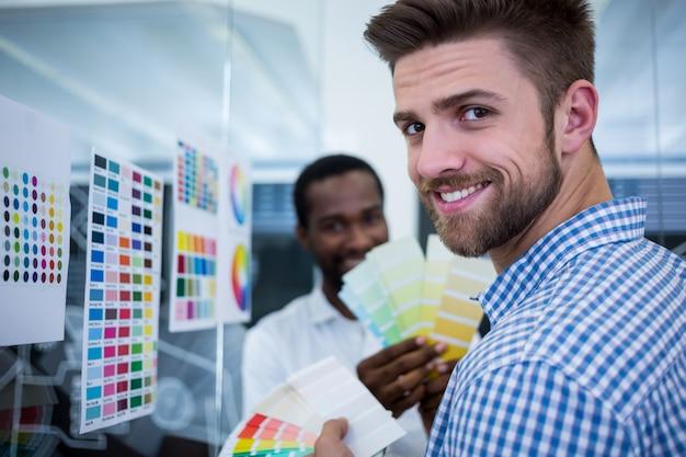 Mężczyzna uśmiecha się z kolorami w ręku