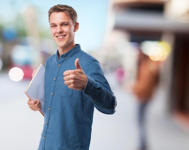 Mężczyzna uśmiecha się z notesem i kciukiem do góry
