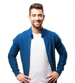 Mężczyzna uśmiecha się z rękami na biodrach