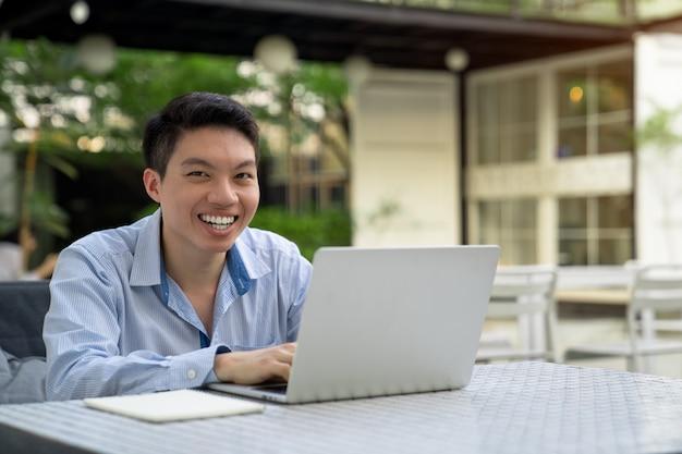 Mężczyzna uśmiecha się, za pomocą laptopa.