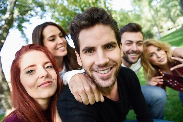 Mężczyzna uśmiecha zrobieniem zdjęcia siebie z nim i jego przyjaciółmi z drzewami w tle