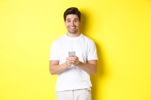 Mężczyzna uśmiechający się i wyglądający na szczęśliwego po przeczytaniu oferty promocyjnej na smartfonie, stojący na żółtym tle w białej koszulce.