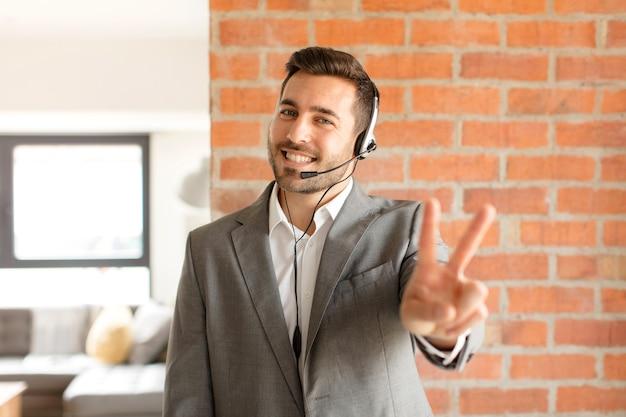 Mężczyzna uśmiechnięty i wyglądający na szczęśliwego, beztroskiego i pozytywnego, gestykulując jedną ręką zwycięstwo lub pokój