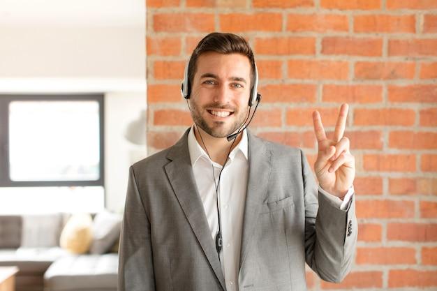 Mężczyzna uśmiechnięty i wyglądający przyjaźnie, pokazujący numer dwa lub sekundę z ręką do przodu, odliczający