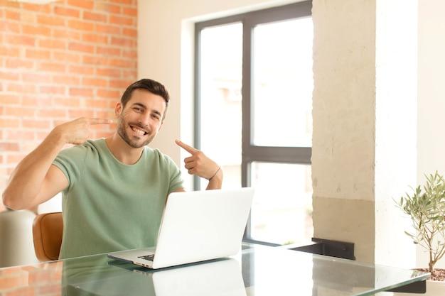 Mężczyzna uśmiechnięty pewnie wskazujący na swój szeroki uśmiech, pozytywne, zrelaksowane, usatysfakcjonowane nastawienie