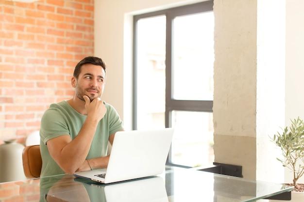 Mężczyzna uśmiechnięty ze szczęśliwym, pewnym siebie wyrazem twarzy z ręką na brodzie, zastanawiający się i patrzący w bok