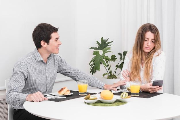 Mężczyzna uspokaja kobiety przy stołem
