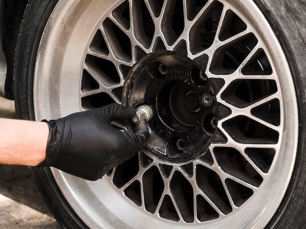 Mężczyzna usuwa nakrętki koła samochodu