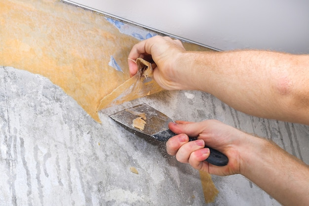 Mężczyzna usuwa starą tapetę szpachelką i spryskiwaczem z wodą
