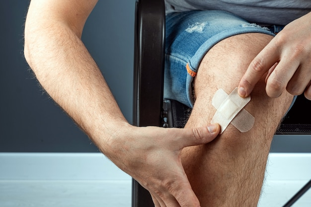 Mężczyzna uszczelnia ranę na kolanie przylepnym tynkiem z bliska. karetka pogotowia, pielęgnacja ciała, urazy kolan.