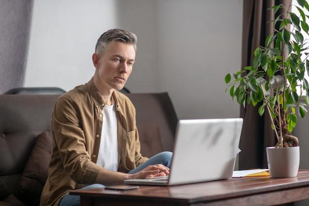 Mężczyzna uważnie patrzący na laptopa w pokoju