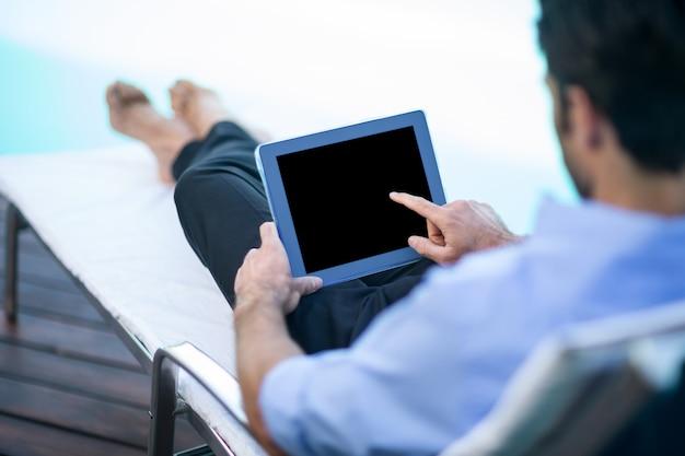 Mężczyzna używa cyfrową pastylkę blisko basenu
