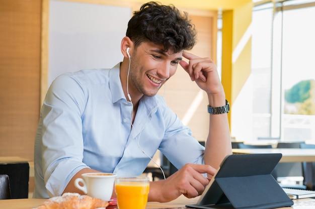 Mężczyzna używa cyfrową pastylkę przy kawowym barem