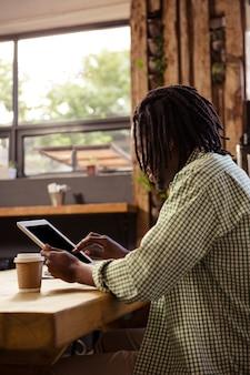 Mężczyzna używa cyfrową pastylkę w bufecie